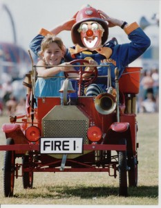 Oh no – a woman driver!! Chief Fire Officer Clown Bluey gets driven 'off-road' by an enthusiastic young lady volunteer.